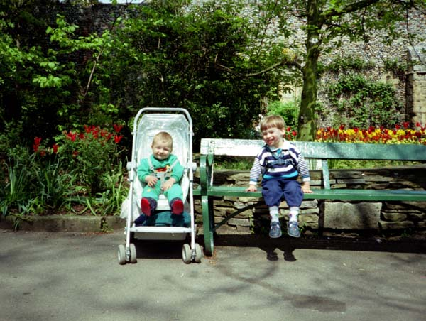 Martin sitting on a bench and Adrian in a pushchair in a park