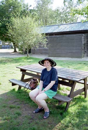Miriam sitting on a picnic bench wearing a wide-brimmed hat