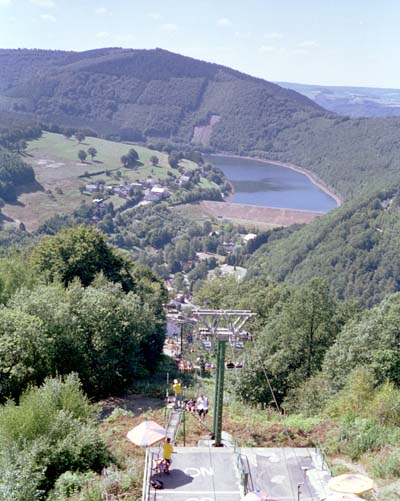 View of a chairlift with a lake at the foot of another mountain in the distance