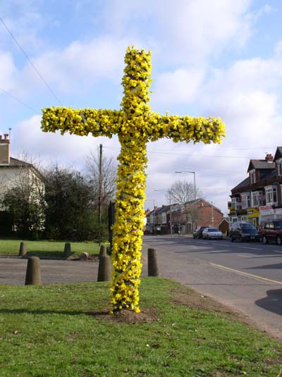 Wooden cross decorated with flowers by the roadside