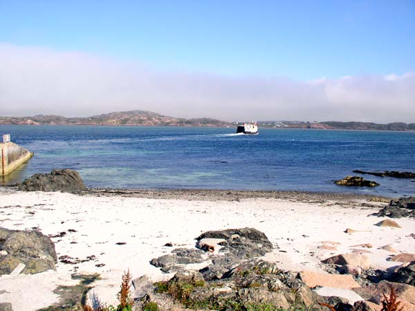 The ferry heads towards Mull, viewed from a white sandy beach on Iona