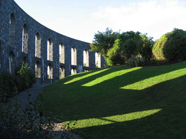 The evening sun shines through the arches of McCaig's Tower, Oban, casting shadows on the ground