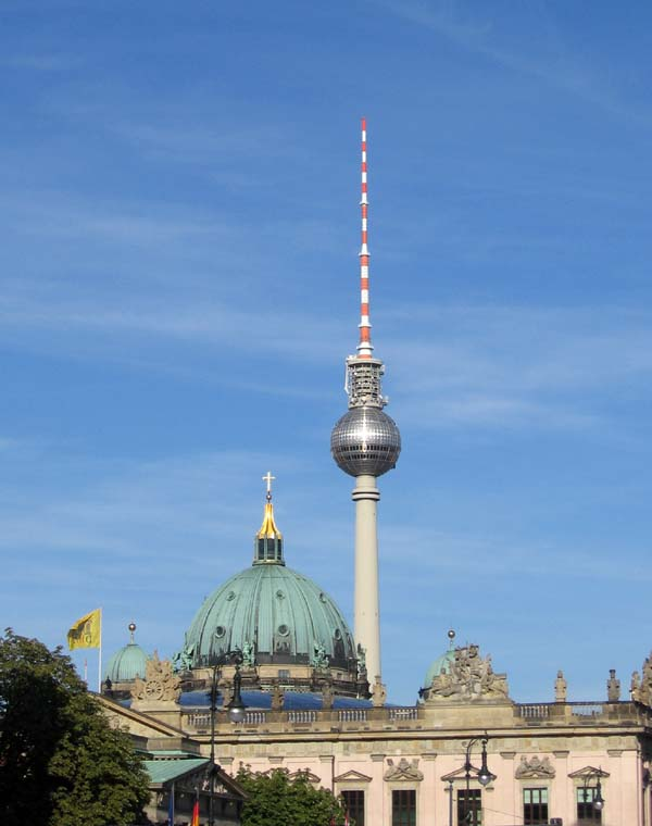 The sun's reflection on the Fernsehturm, Berlin, forms the shape of a cross: nearer the viewer is the cross on top of the dome of the Berliner Dom