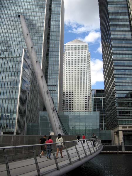 A footbridge leads to skyscrapers and, in the distance, Canary Wharf