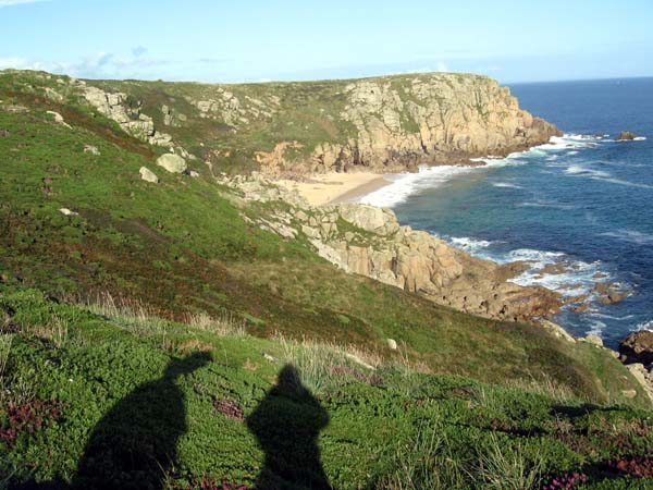 Two human shadows on a sunlit clifftop
