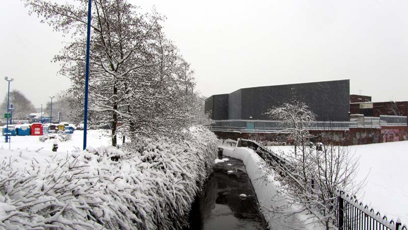 The River Bourn flowing past Stirchley Park in the snow