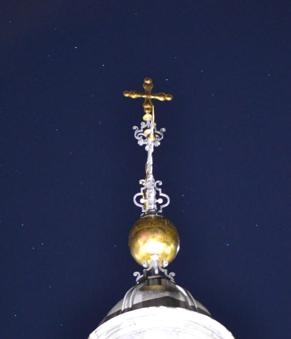 Birmingham Cathedral's newly gilded cross with a starry background