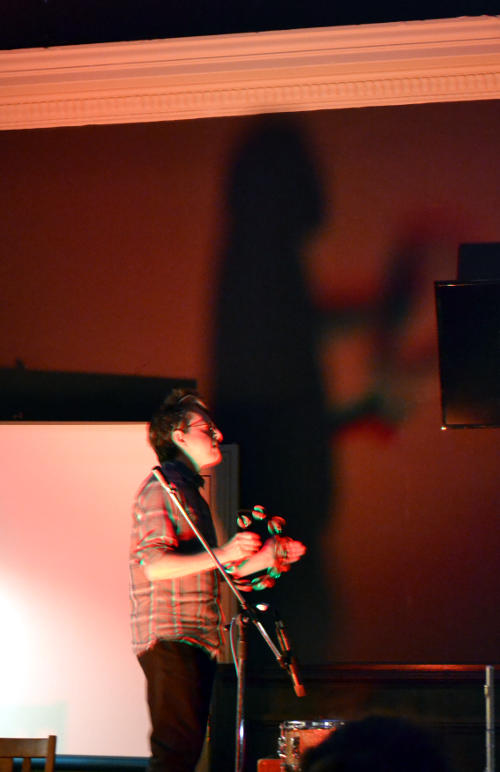 Drummer Rob Peters silhouetted against the back wall