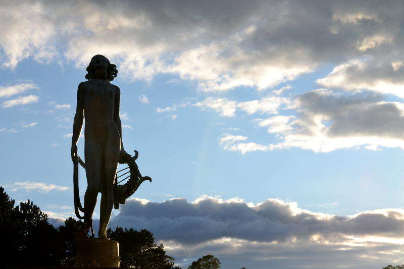 Classical statue in silhouette against the evening sky