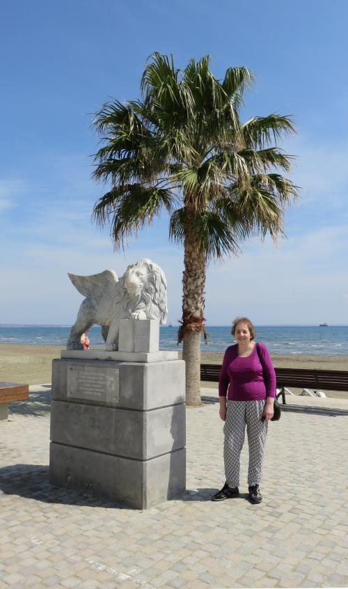 Miriam standing next to a statue by the seafront at Larnaca