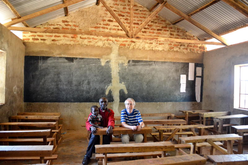 Phil sitting with a local pastor in an otherwise empty classroom