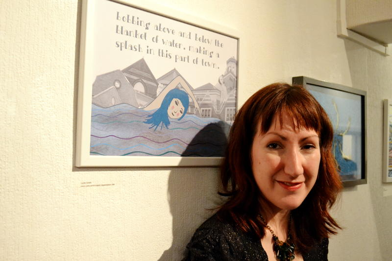 Carla Smith standing in front of her swimming-themed artwork