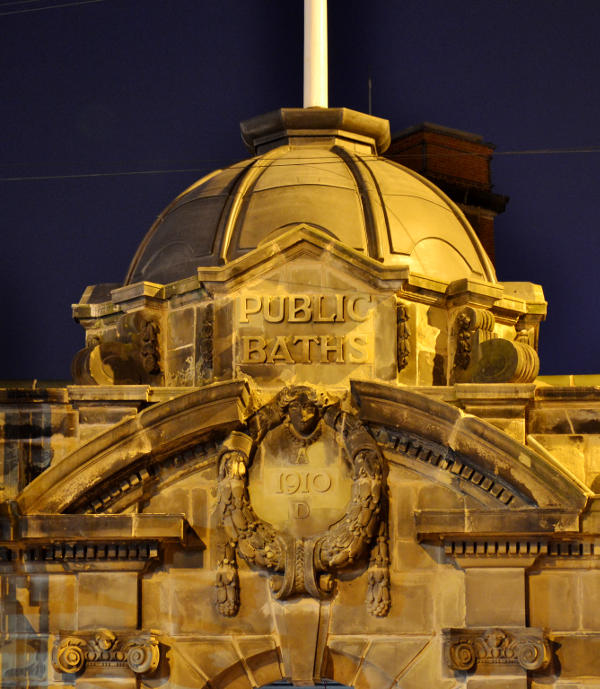 A stone cupola at night under street lighting