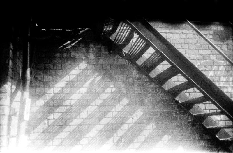 Grainy black and white photo of a metal staircase in sunshine
