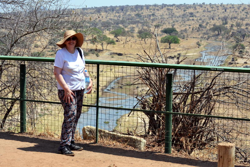 Miriam standing by a metal fence with a river and scrubland in the background