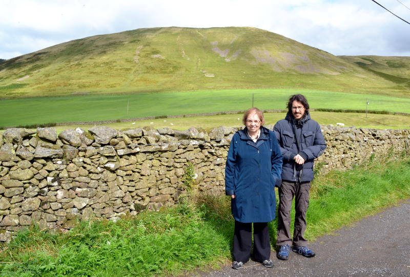 Miriam and Martin standing in front of a dry stone wall with a hill in the background