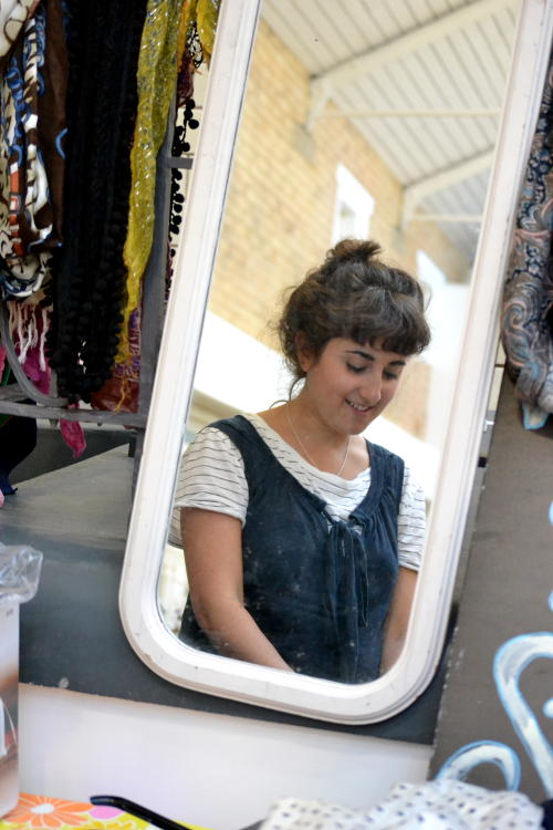 Stallholder reflected in a mirror