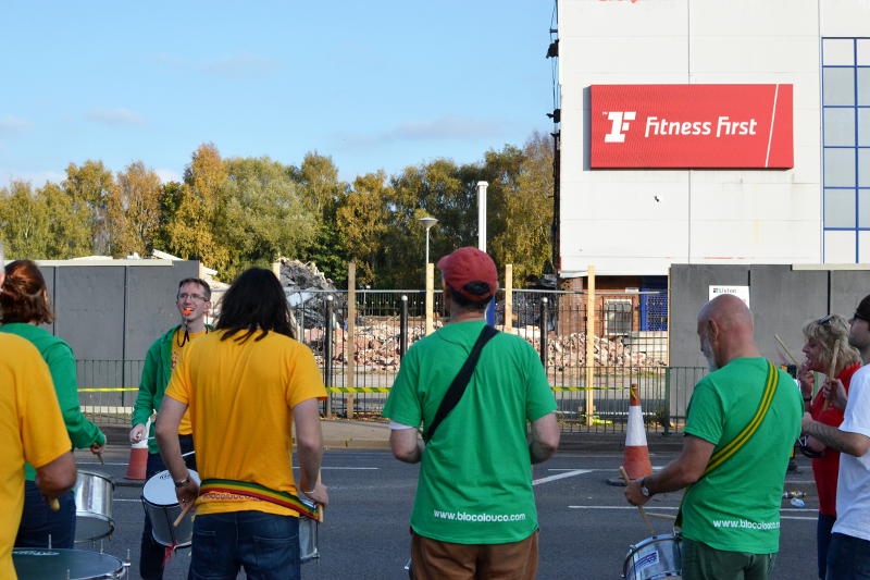 The Bloco Louco drumming group with the remains of Fitness First in the background