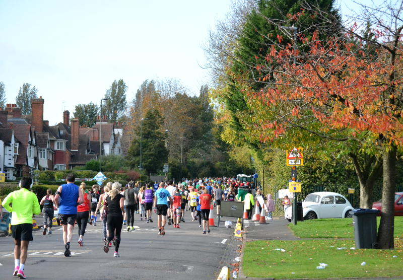 The runners go up Selly Park Road past a tree with brown leaves
