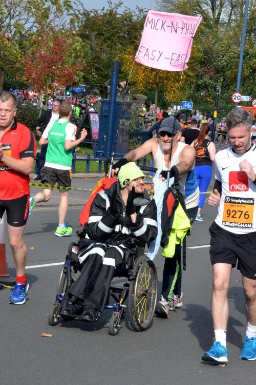 A runner pushing a friend in a wheelchair