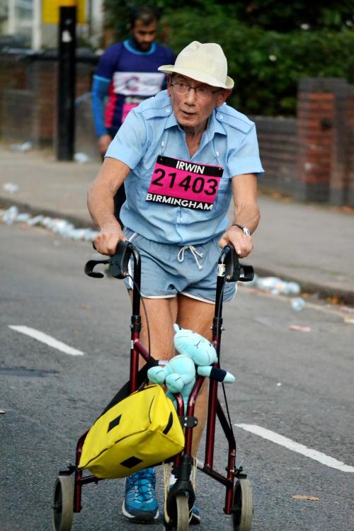 An elderly man pushing a wheeled frame