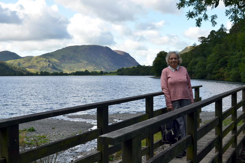 Miriam standing on a wooden bridge with Buttermere in the background