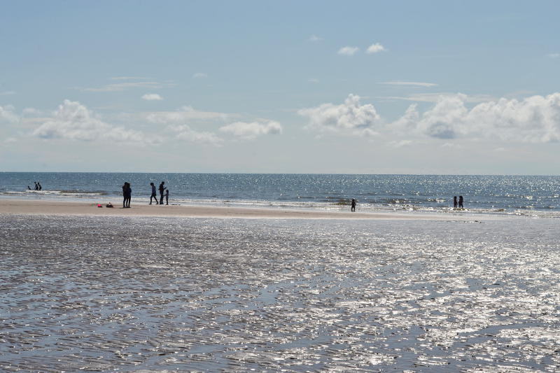Sunshine reflected off sea and wet sand
