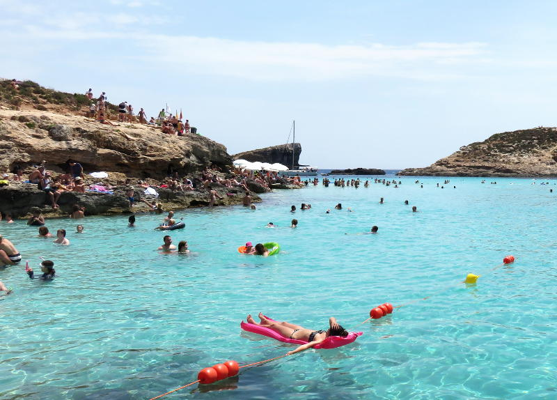 The crowds pack around the Blue Lagoon on Comino island