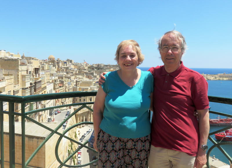 Miriam and Phil on a balcony with the city of Valletta in the background