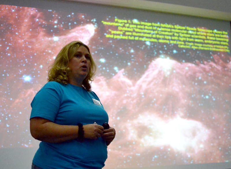 Dr Helen Fraser speaking in front of a screen displaying a nebula