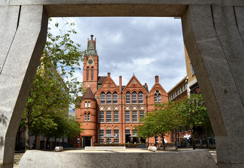 A traditional school building viewed through the frame of a sculpture