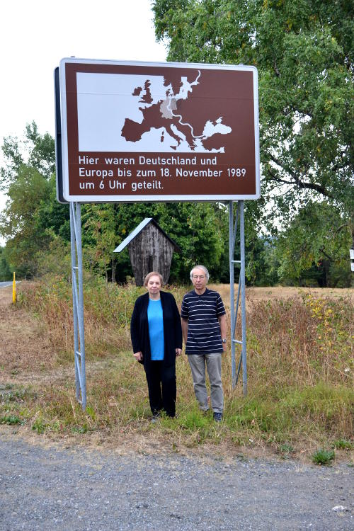 Miriam and Phil in front of a sign marking the former border between East and West Germany