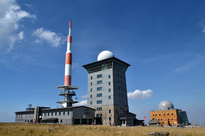 Two buildings with radomes on top, and a radio mast