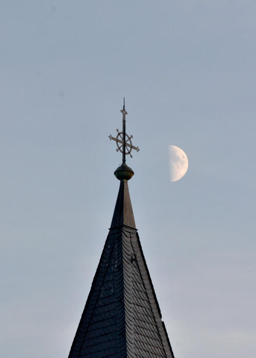 The Moon next to a church spire