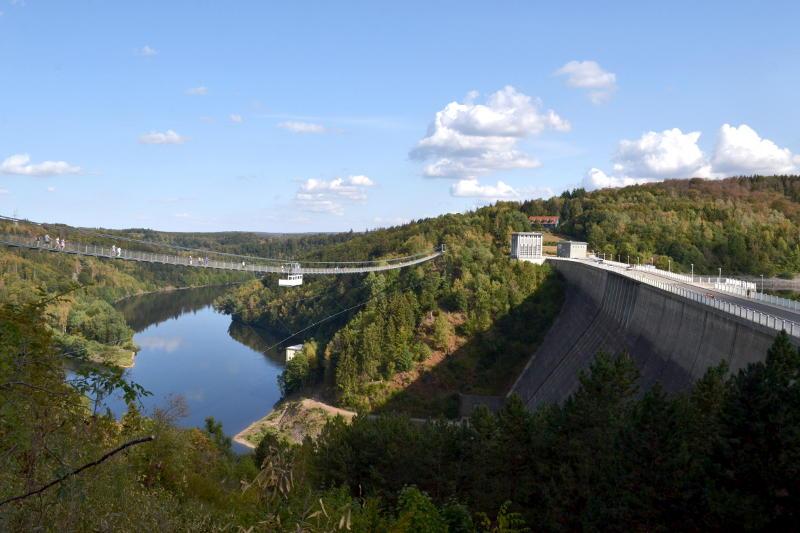 A reservoir dam with a passenger bridge alongside it