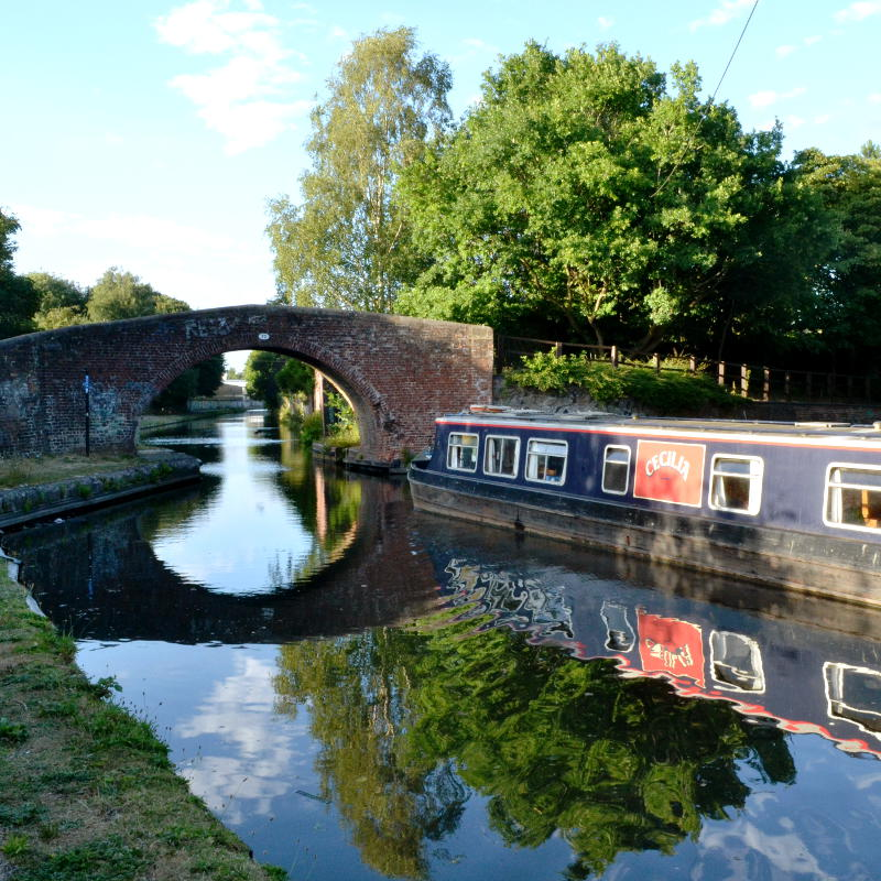 A canal boat heading under an arch bridge