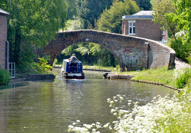 A boat going under an arch bridge