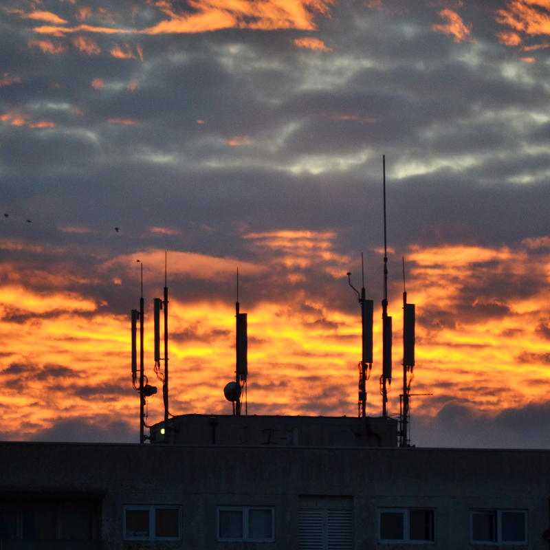 Mobile phone masts silhouetted against a cloudy sunset