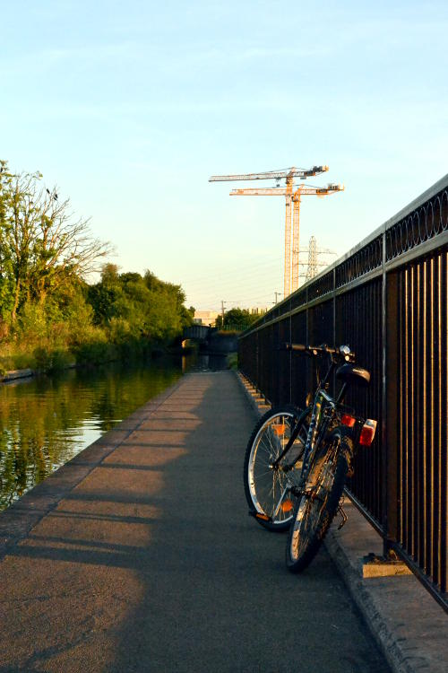 A bike leaning on railings with cranes in the background