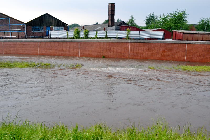 Water forced into the River Rea by a flood defence wall