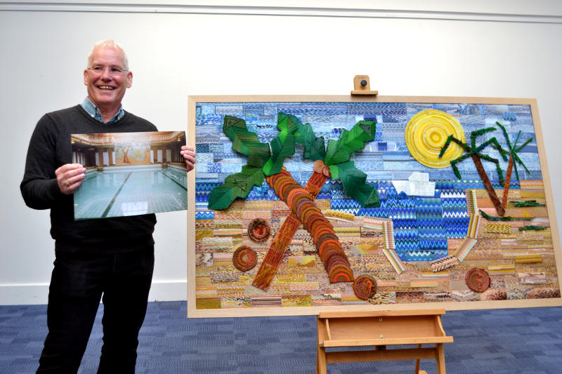 Paul Jones standing beside a tapestry showing a tropical scene