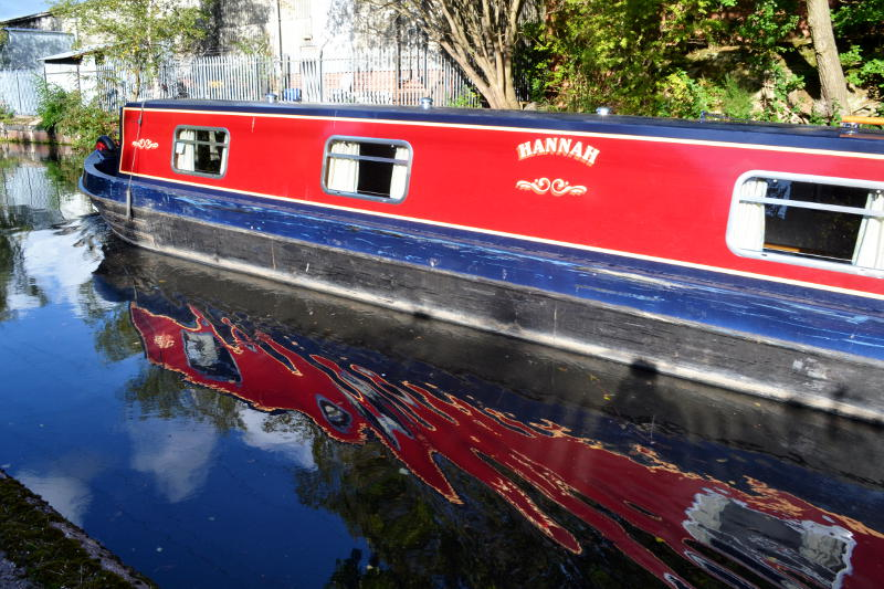 A canal boat with distorted reflection in the water