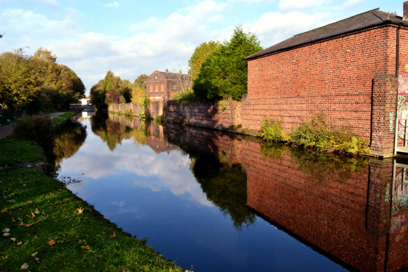 A brick wall and building reflected in the water of the canal