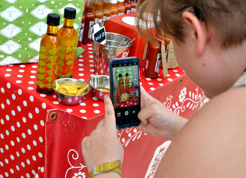 A photo of a stall being taken on a mobile phone