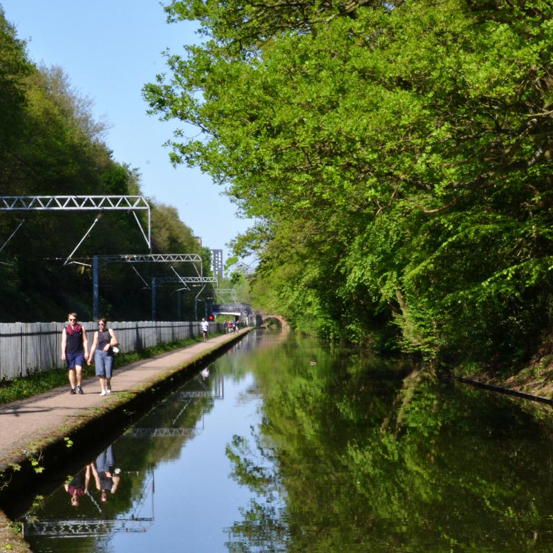 Walkers on the towpath between the canal and the railway