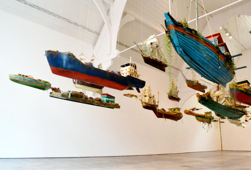 A collection of model boats hanging from the ceiling of an art gallery