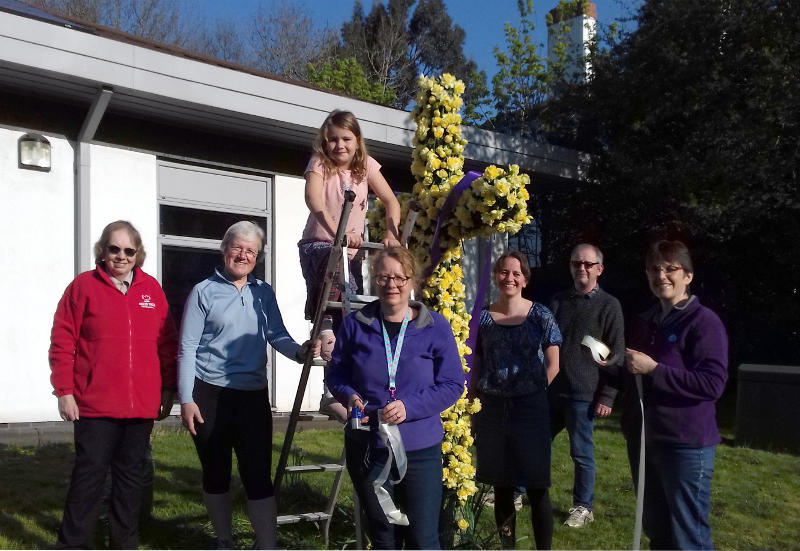 Miriam and friends standing next to a cross that is covered with daffodils