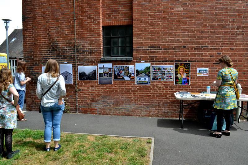 Photos on display along a wall