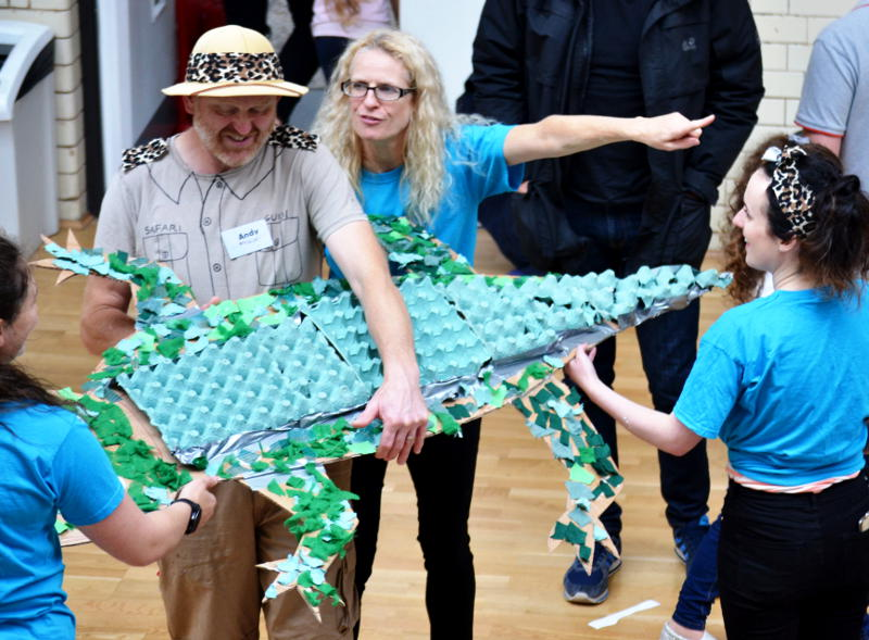 A group holding a model alligator