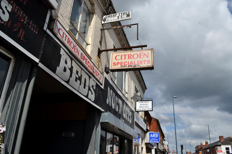A mixture of shop signs projecting above the pavement